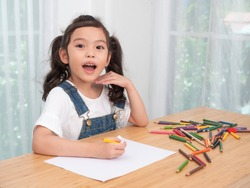 Asian little cute girl sitting and use color pencil drawing cartoon in white paper on wooden table. Preschool lovely kid with  drawing at paper near the window. Learning and education of kid.