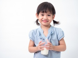 Asian little cute girl 4 years old holding and drinking milk from glasses over white background. Milks is essential and nutrition for the child's body.