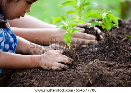 Asian little girl and parent planting young tree on black soil together as save world concept - Shutterstock ID 654577780