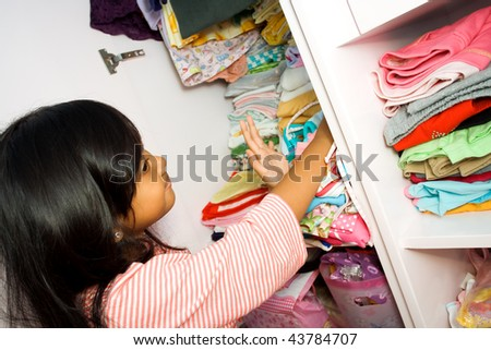asian little girl arranging her clothes collection in the closet