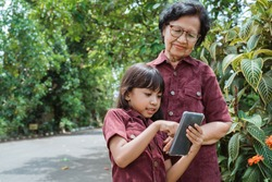 asian little girl enjoy watching a video using cell phone with her grandma