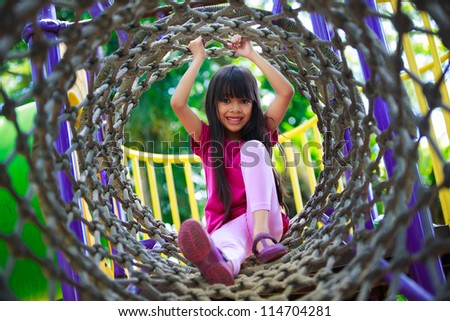 Asian Little Girl Enjoys Playing In A Children Playground, Outdoor Portrait