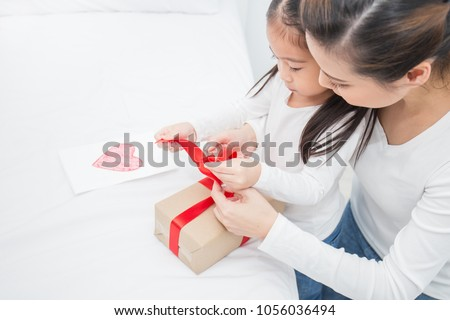 Asian little girl help her mother open gift box, celebration holiday christmas mother\'??s day concept.