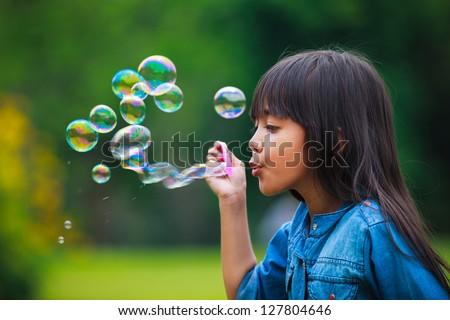 Asian little girl is blowing a soap bubbles, Outdoor Portrait Stock foto ©