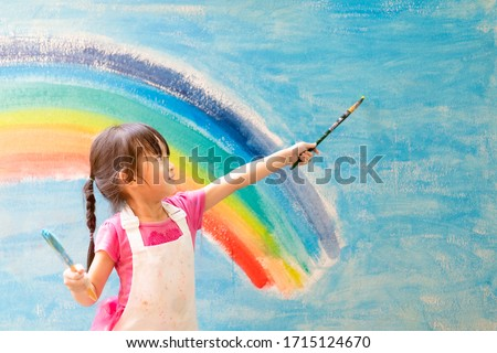 Asian little girl is painting the colorful rainbow and sky on the wall and she look happy and funny, concept of art education and learn through play activity for kid development. Foto stock ©