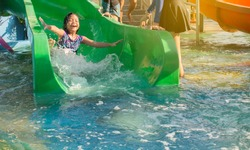 Asian little girl playing water slide in water park on summer holiday