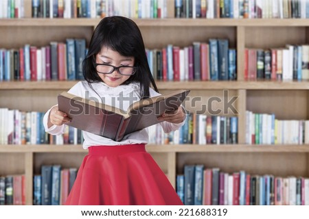 Asian little girl reads book seriously in library with bookcase background