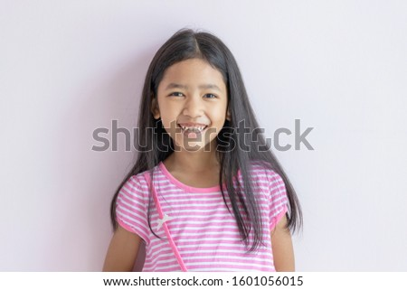 Asian little girl smiling brightly. Children wearing pink cross white dresses and long black hair. The child looks ahead and smiles happily. Portraits of cute Asia kid laughing and smiled.