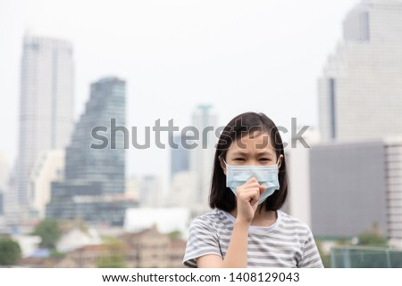 Asian little girl suffer from cough with face mask protection,cute child wearing face mask because of air pollution in the city building,Sick girl with medical mask;concept of pollution,dust allergies #1408129043