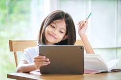 Asian little girl taking class on line and happy for Homeschool Quarantine coranavirus pandemic concept