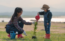 Asian little girl with mom planting and watering tree in nature. First learning of little children. Happy family concept.