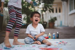 Asian little toddler boy is crying while he playing the watercolor paint at home and he unhappy to the play messy, concept of experience, bully, and mental health in childhood.