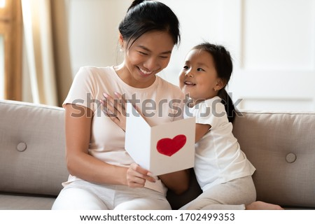 Asian lovely sweet preschool daughter congratulates mommy with life event birthday holiday, prepares for her handmade post card with red painted heart symbol of unconditional love, Mother Day concept