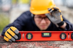 Asian maintenance worker man holding red aluminium spirit level tool or bubble levels at construction site. Equipment for civil engineering project