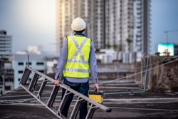 Asian maintenance worker man with safety helmet and green vest carrying aluminium step ladder and tool box at construction site. Civil engineering, Architecture builder and building service concepts