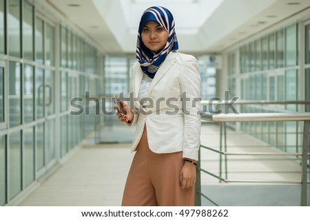 Asian (Malay) Muslim Woman wearing Headscarf using Mobile Phone #497988262