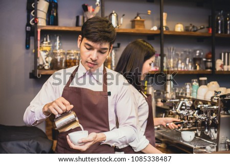 Asian male barista making coffee in coffee shop counter.  Barista male working at cafe. Man working with small business owner or sme concept. Vintage tone.