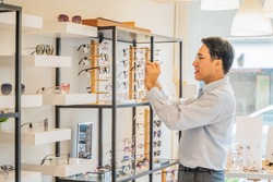 asian male client chooing new eyeglasses frame for his new eyeglasses in optical store