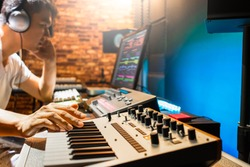 asian male composer playing midi keyboard synthesizer for making music in sound studio
