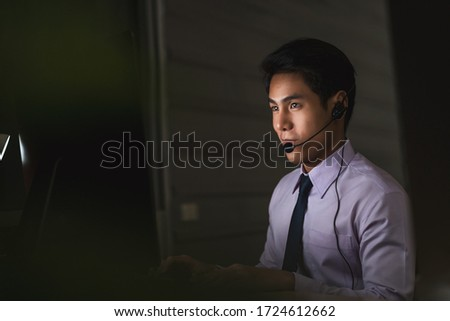 Asian male customer care service smiling and working hard late in night shift at office, call center department,worker and overtime, 7 days 24 hour support,teamwork with colleagues for success concept