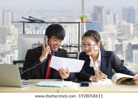 Asian male employee is answering the phone from customer while asking for advice from superior team leader for after sale service Foto d'archivio ©