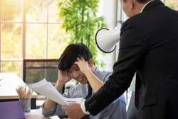 Asian male employers and employees are arguing about the wrong job. The irritated supervisor blames his subordinates for their delayed work and missed the deadline. Quarreling in the office.