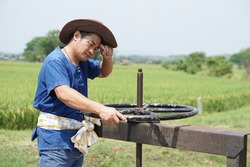 Asian male farmer is turning the wheel of water gate to launch water to his rice paddy field in rural farmland in Thailand. Feeling tired and hot. Concept agricultural occupation. farmer working.