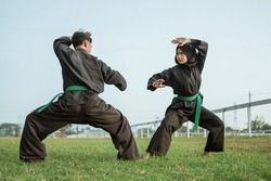 Asian male fighter wearing a pencak silat uniform with side stance poses against a hooded female fighter with side stance in an outdoor background