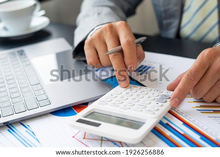 Asian male finance staff is calculating by using a calculator. Investment results to report to his boss at the meeting. On the table in the office, the concept of calculating investment results