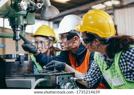 Asian male foreman manager showing case study of factory machine to two engineer trainee young woman in protective uniform. teamwork people training and working in industrial manufacturing business ストックフォト ©
