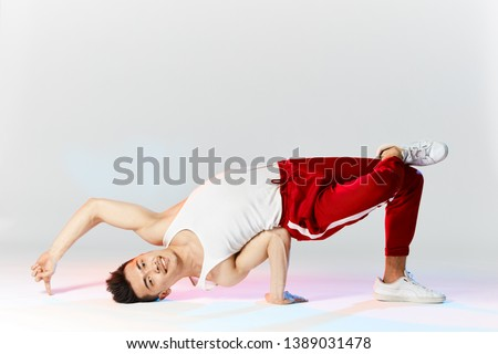 Asian male hip hop dancer or bboy freezes in Air Baby pose on the hand posing over white studio background #1389031478