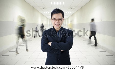 asian male in a tunnel with people walking in hurry