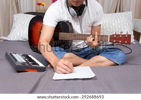 asian male music composer, musician writing song & playing guitar on bed in bedroom