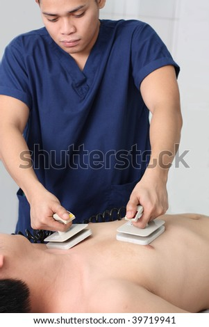 asian male nurse resuscitating a patient with a defibrillator