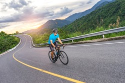 asian male riding on a black bicycle along the winding road up a hill, wearing a cycling blue jersey, crash helmet and goggles, sunset light, grey sky, and forest trees and mountains in the background