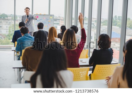 Asian male speaker is speaking at seminars and workshops to the people in the meeting. Participants are raising their hands to ask questions. #1213738576