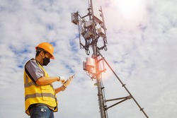 Asian male worker engineer wearing a helmet and safety goggles uses a smartphone to field work near a telecommunication tower controlling cellular electrical installations.
