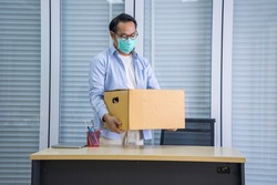 Asian male worker wearing a mask, holding a storage box, moving things out to work because he was kicked out of the economic downturn due to covid19 disease outbreak.