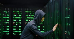 Asian male young hacker breaking security code with smartphone while standing at servers in dark room. Man in hood hacking server with database of private information. Spyware concept.