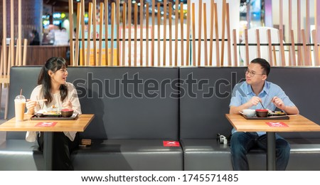 Asian man and woman eating food on table by one person one table for social Distancing 6 feets concept protection of Coronavirus Covid-19 at food court in Bangkok, Thailand.