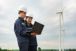 Asian man and woman Inspection engineers preparing and progress check with laptop of a wind turbine with safety in wind farm in Thailand.