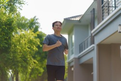 Asian man are jogging in the neighborhood for daily health and well being, both physical and mental and simple antidote to daily stresses and to socialize safely.