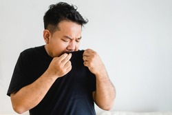 Asian Man body with sweat on black t shirt workout fit from home.bad smell breathing on armpit with black shirt.indian man smelly.hyperhidrosis, deodorant, Medical health.Men Skin body care.