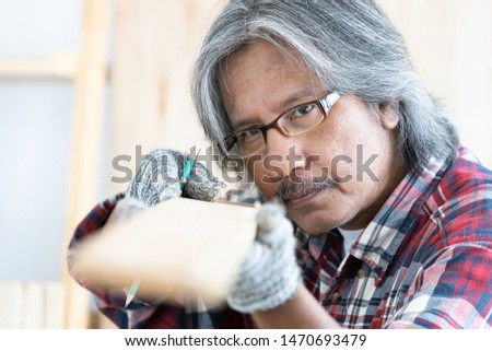 Asian man carpenter working on woodworking table in home carpentry shop, Old asian man works in home carpentry shop. #1470693479