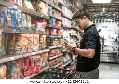 Asian man choosing instant noodle in supermarket, Steward shopping alone at supermarket, Choosing food in market, Shopping alone in food store, Dried food in supermarket, Market in shopping mall