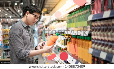 Asian man choosing orange juice in supermarket using smartphone to check shopping list. Male shopper with shopping cart selecting beverage bottle product in grocery store.