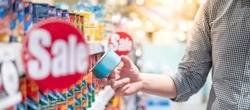 Asian man customer choosing canned food from shelf in supermarket or grocery store. Hoard instant food for quarantine at home during Coronavirus (COVID-19) pandemic. Consumerism concept