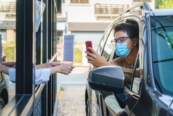 Asian man customer using mobile scan QR or NFC payment on smart phone paying for his coffee drink in coffee shop while he drive thru and Barista wearing mask in background