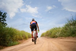 Asian man cycling on gravel road.