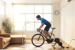 Asian man cyclist. he is exercising in the house and  trainer and play online bike games.He stood up spinning